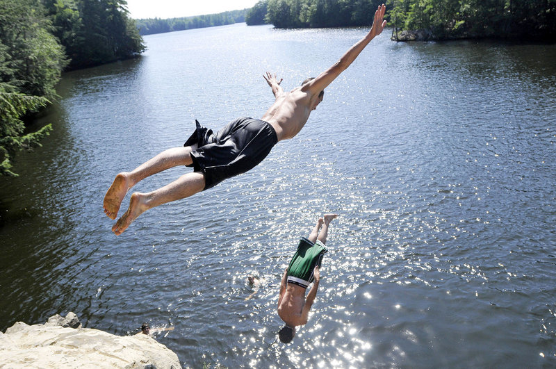 Matt LeBlanc of Dayton dives as Matt Jervis of Lyman does a backflip into the Saco River from a cliff at Pleasant Point Park in Buxton on Friday.