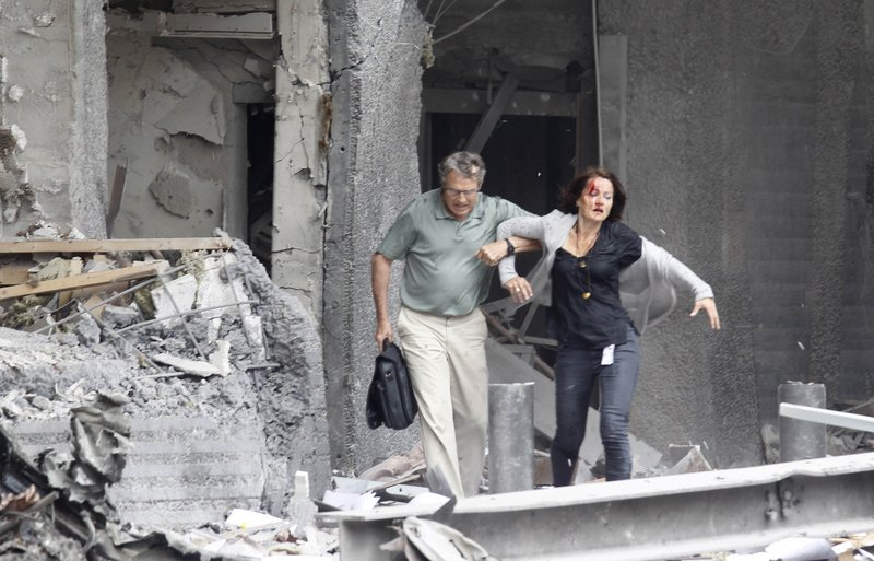 An injured woman is assisted from a damaged building in Oslo on Friday, after an explosion rocked the Norwegian capital. Terrorism struck long-peaceful Norway when a bomb ripped open buildings including the prime minister's office, and a man dressed as a police officer opened fire at a nearby island youth camp. At least 80 people were killed.