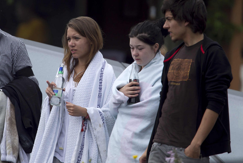 Unidentified survivors from the shooting at an island youth retreat stand wrapped in blankets outside a hotel where survivors were being reunited with their families in Sundvolden, Norway, on Saturday.