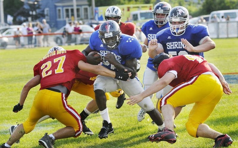 Imadhi Zagon of Portland, who scored two touchdowns for the West during the Lobster Bowl on Saturday at Biddeford, threads through two defenders – Brandon Higgins of Orono, left, and Jacob Halberg of Camden Hills. The West won, 16-13.