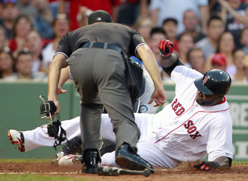David Ortiz of the Red Sox is out at home plate on a throw from Seattle's Franklin Gutierrez after a fly out by Jason Varitek in the second inning Saturday night at Fenway Park.