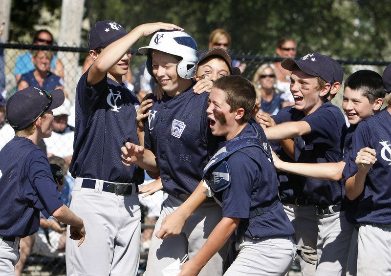 Luke Klenda, third from left, celebrates with teammates after hitting a solo home run in the second inning Sunday against York in the Little League state tournament for 11 and 12 year olds. Yarmouth went on to beat York, 2-1.