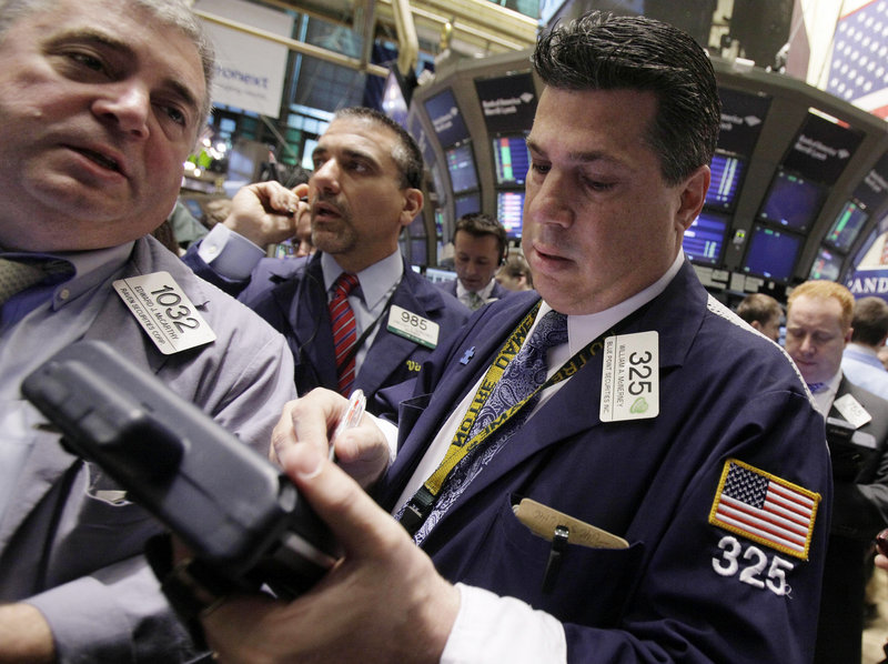 Traders Edward McCarthy, left, and William McInerney, right, work on the floor of the New York Stock Exchange. There has been less work to do lately: Volume in July is down 1 billion shares a day from July 2010.