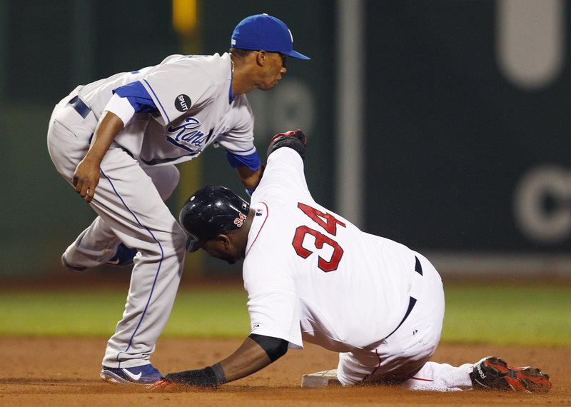 Alcides Escobar, left, makes the tag as David Ortiz is caught trying to steal second base in the fourth inning Monday night in Boston. The start of the game was delayed 2 hours, 21 minutes by a passing rain shower.