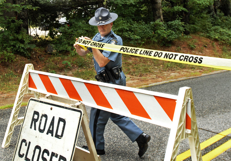 State Trooper Steven Green seals off a part of Bennett Road in New Gloucester while investigators collect shooting evidence Tuesday.