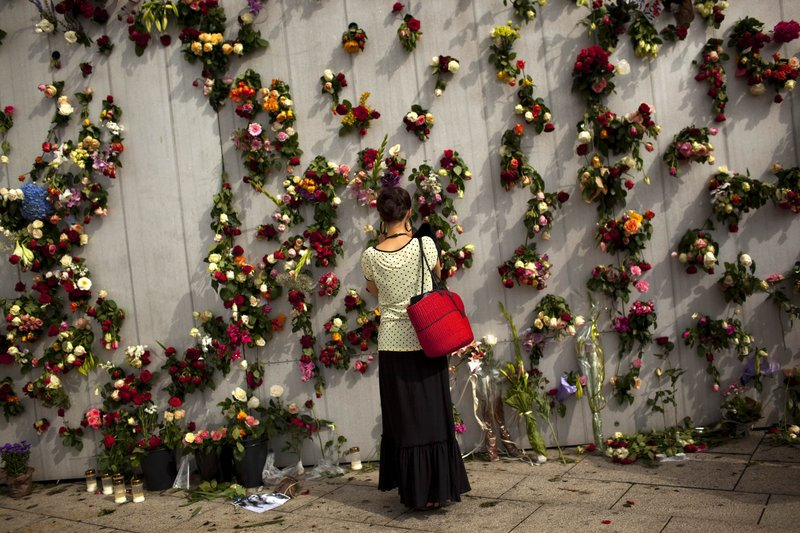 A woman pays respects at a wall decorated with flowers in memory of the victims of Friday's bomb attack and shooting rampage in Oslo, Norway, on Tuesday.