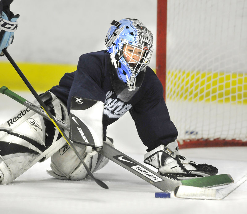 Sam Tibbetts blocks a shot while working on his goaltending technique. Tibbetts is one of 52 boys and girls attending the morning and afternoon sessions.
