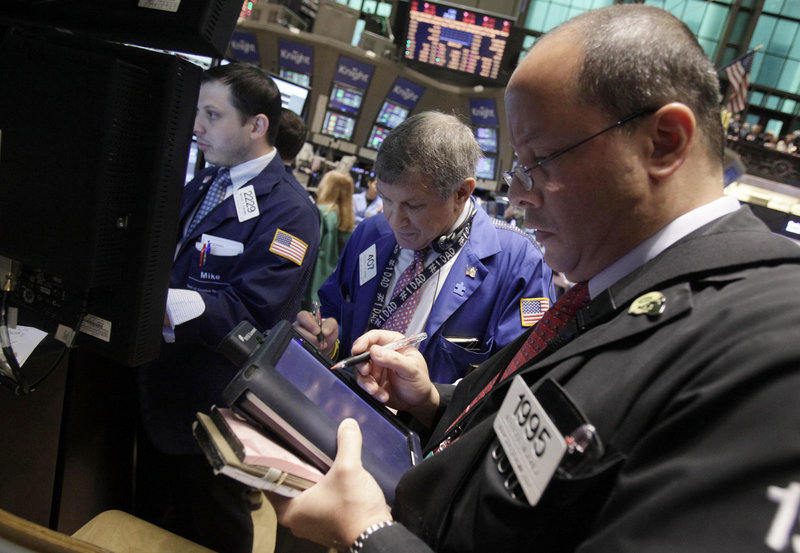Specialist Michael Pistillo, left, calls out prices as he works on the floor of the New York Stock Exchange Wednesday. Analysts say the stock market will get more volatile as the weekend nears and no debt-ceiling deal is reached.