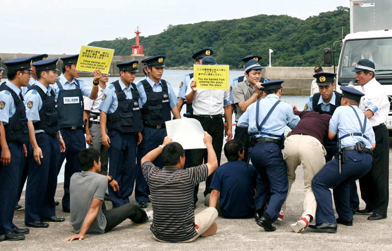 "Japanese officers block mock protesters during a security drill Wednesday in Taiji, a village under fire for dolphin hunts. About 100 police and coast guard officers gathered in the bay – the scene of an Oscar-winning film ""The Cove."""