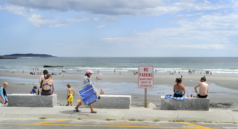 A sparse crowd takes in a spectacular day last week at Higgins Beach in Scarborough. Scant parking has always limited public access to the beach, which is fronted by private landowners but used by the public since the 1800s.