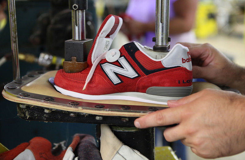 A worker uses a press to attach a shoe upper to the outsole at the New Balance factory in Norridgewock. Since 2004, the 350 workers at the plant have increased daily production by nearly 9 percent.