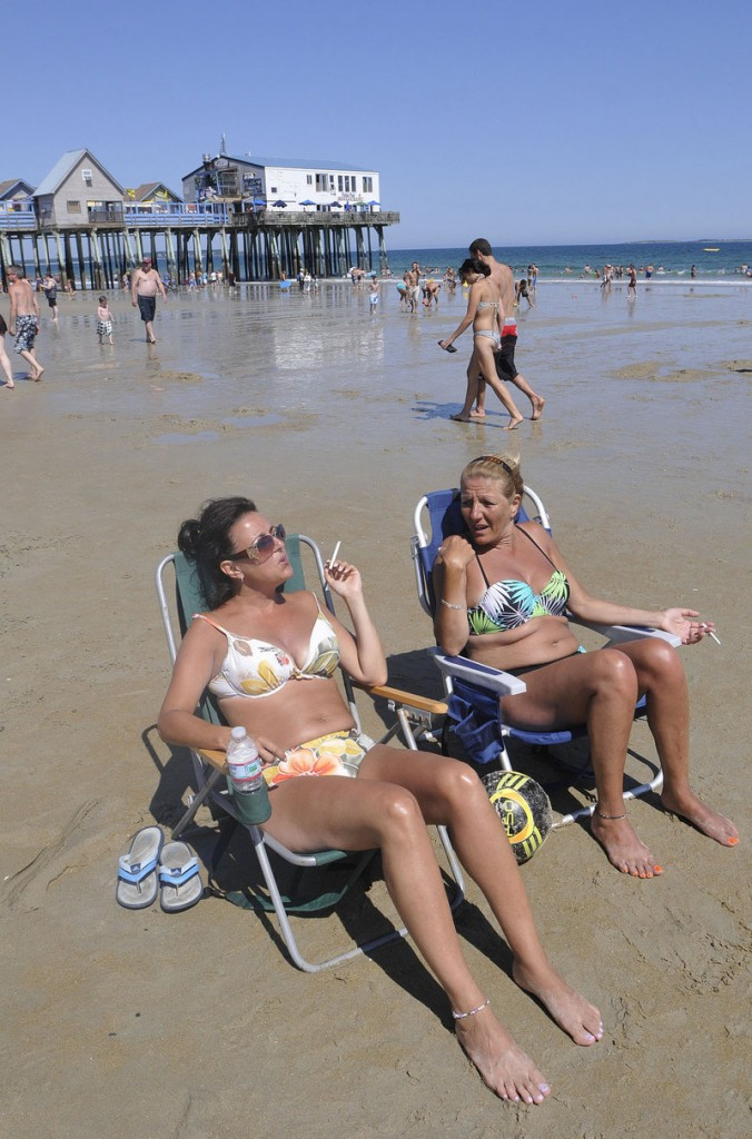 Rita Tamburro and Josie Gentile, both of Montreal, smoke while relaxing at Old Orchard Beach Thursday. Seventy-three Maine communities already ban smoking at recreation areas like beaches.