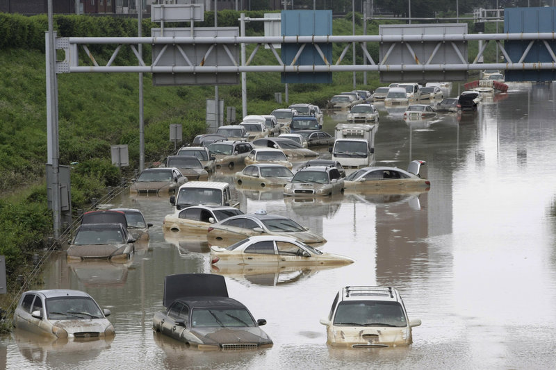 Vehicles are partially submerged after heavy rain in Seoul, South Korea, on Thursday. Rescuers cleared mud to search for survivors after landslides and flooding killed 57 people.
