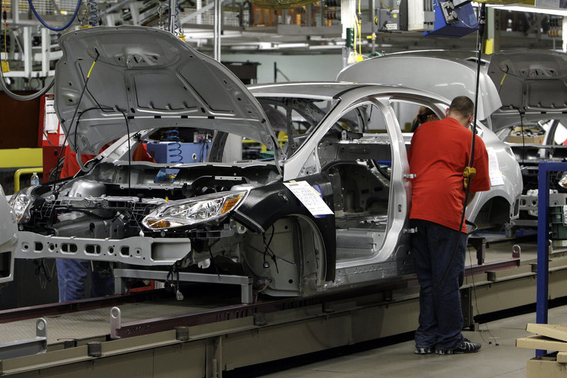 A line worker assembles a 2012 Ford Focus at the assembly plant in Wayne, Mich. The dashboards for the car are in short supply because of machinery problems.