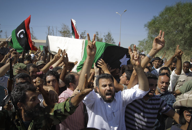 Libyans chant slogans during the funeral of the rebels' slain military chief, Abdel-Fattah Younis, in the rebel-held town of Benghazi on Friday. Younis was killed under mysterious circumstances while in custody by rebels.