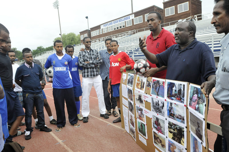 Mohamud Barre, executive director of the Somali Culture and Development Association of Maine, shows photographs from Somalia and speaks with soccer players prior to their games Friday.