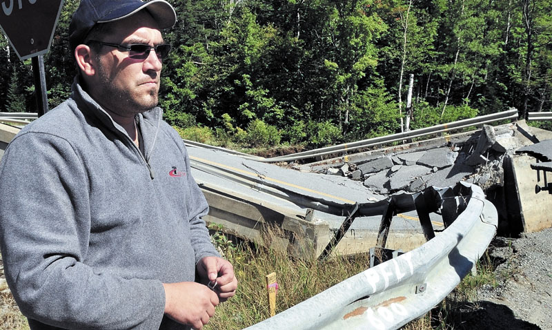 CLOSE CALL: Truck driver Yannick Livernoche of Quebec on Monday talks beside a collapsed bridge over the Carrabassett River on Route 27 in Carrabassett Valley.