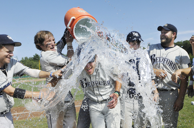 Bedford Post Coach Tim Conway gets a shower after the game, courtesy of his players, during the team's championship celebration. Bedford moves on the American Legion World Series in Shelby, N.C.