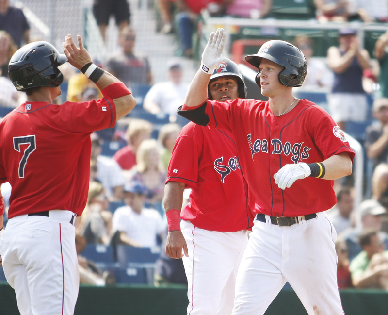 Jeremy Hazelbaker of the Sea Dogs is congratulated by Mark Wagner, left, and Ronald Bermudez after hitting a three-run homer in the fifth inning today against the Binghamton Mets at Hadlock Field. The Sea Dogs lost, 7-6.