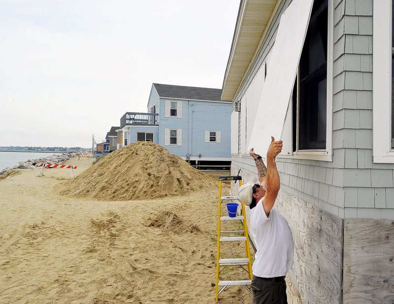 Joe Harvey, owner of Harvest Homes Property Management Co. in Portland, installs plywood window protectors on a client's house on Surf Street in Camp Ellis on Saturday in preparation for Irene. The pile of sand was dumped in front of the street to help prevent flooding. Along the Eastern Seaboard, cities shut down transportation systems and ordered evacuations.