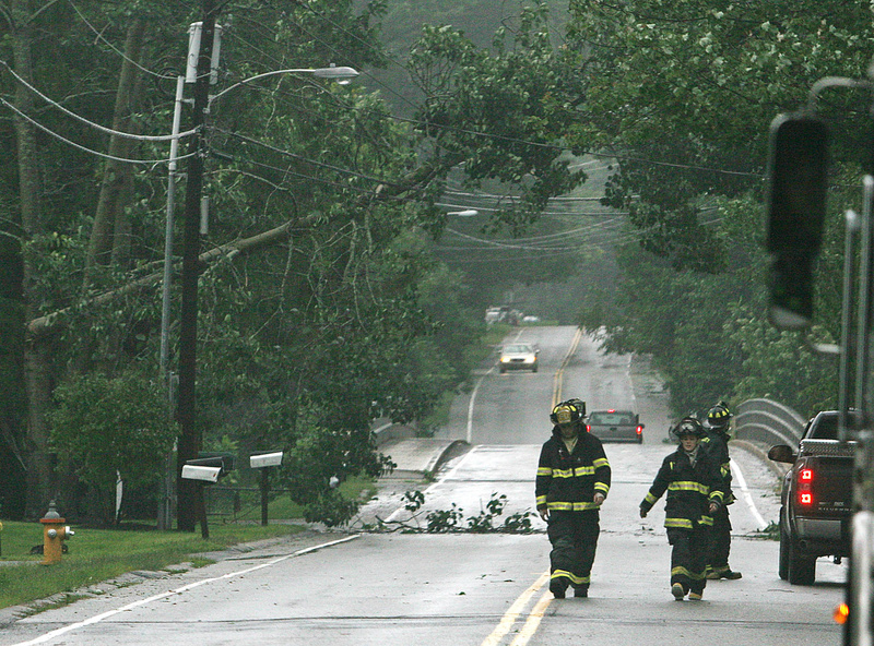 Emergency personnel secure a portion of Leighton Road in Falmouth due to a tree that fell across wires today during Tropical Storm Irene.