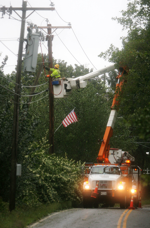 A Central Maine Power Co. lineman repairs lines pulled down by wind-blown trees and branches on Route 35 today.