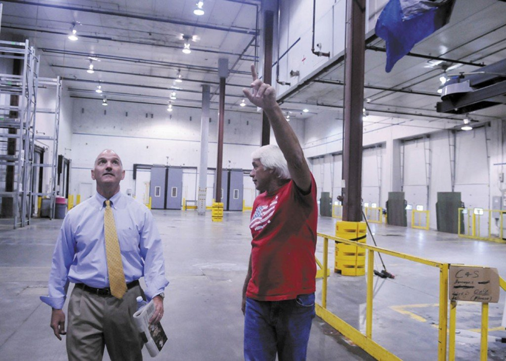 TOUR: Nick Alberding, managing partner and an owner of Pine State Trading, left, gets a tour Monday through the refrigerated storage at the former Associated Grocers warehouse from former AG employee Tom Doucette before an auction for AG's buildings in Gardiner. Camden National Corporation, which held a bank note on the property, made the highest bid.