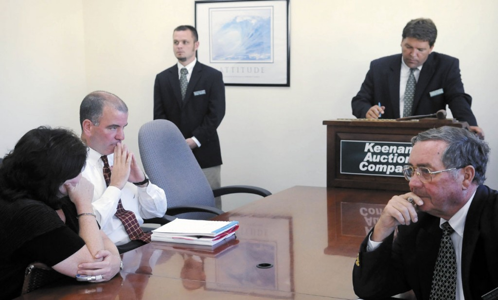 AUCTION: Camden National Corporation senior vice president Stephen Matteo, second from left, waits Monday for Keenan Auction Company employees, right, to close the bidding for the former Associated Grocers of Maine buildings in Gardiner during an auction for AG's real estate. Camden National Corporation, which held a bank note on the property, made the highest bid.
