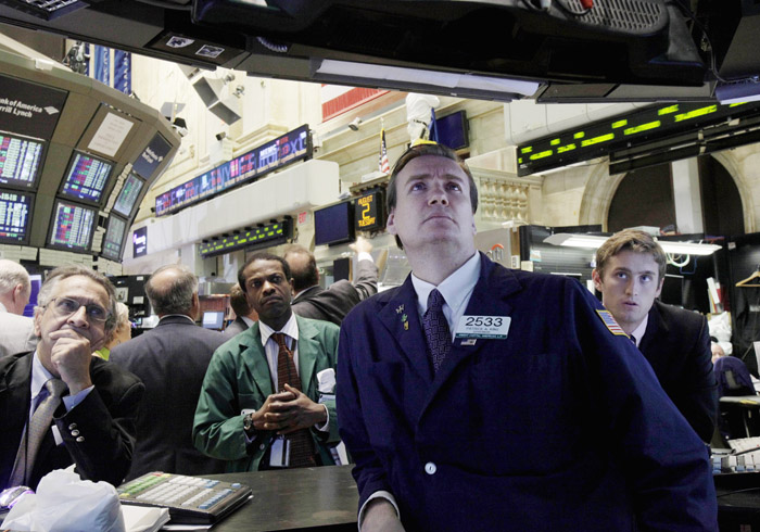 Specialist Patrick King, second from right, and others watch President Barack Obama's remarks on a television monitor the floor of the New York Stock Exchange. The stock market stumbled again today and is on pace for its longest losing streak in two years.