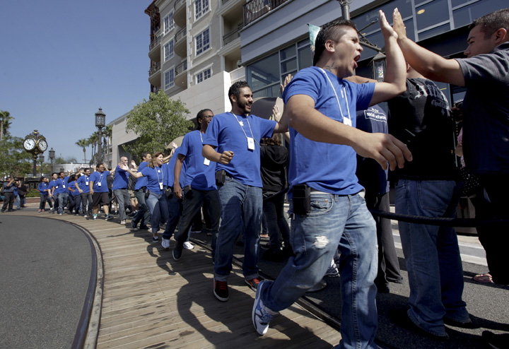 Apple store employees greet customers waiting in line for the grand opening of the 50th Apple store in California at The Americana at Brand in Glendale recently. Hundreds of excited customers lined up despite the fact that there was already an Apple Store a few blocks away.
