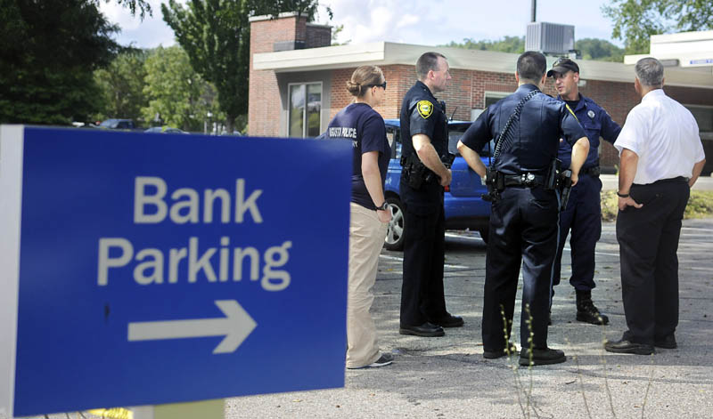 CASH AND CARRY: Police confer Monday in the parking lot of the Bangor Savings Bank branch on Capitol Street in Augusta. Police are investigating a report that a man demanded money from the bank and fled on foot shortly before 10:30 a.m. No weapon was displayed, according to police.