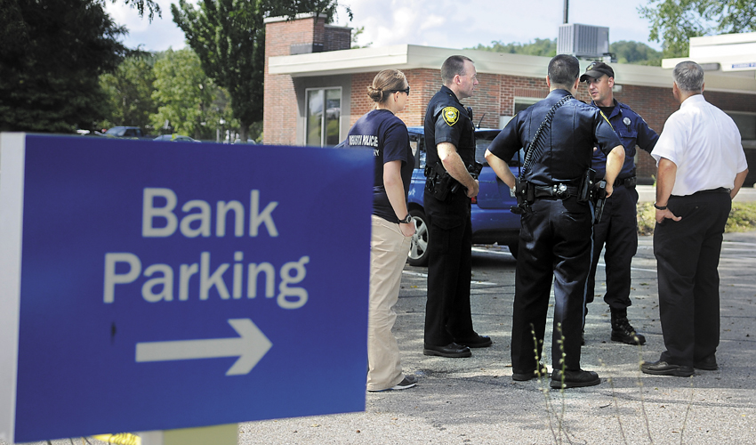 Staff photo by Andy Molloy Police confer in the parking lot Monday of the Bangor Savings Bank branch on Capitol Street in Augusta. Police are investigating a report that a man demanded money from the bank and fled on foot before 10:30 a.m. No weapon was displayed, according to police.