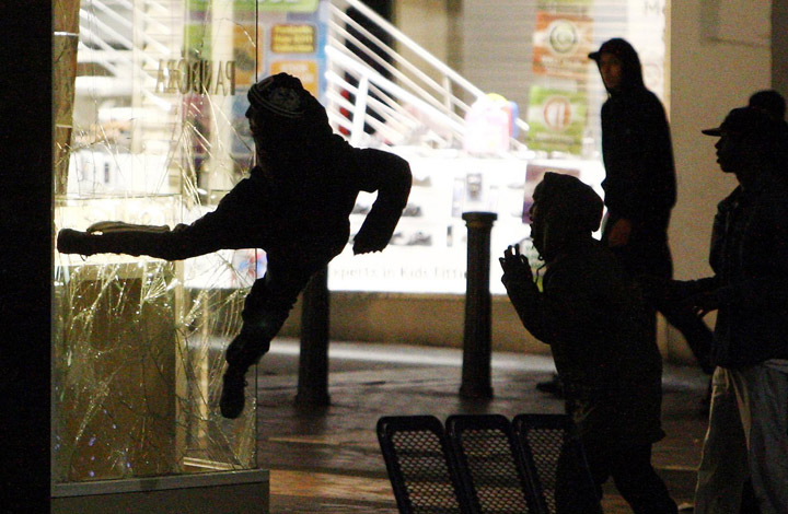 A youth kicks the window of a jewelry store near the Bullring shopping center in Birmingham, England, Monday evening.