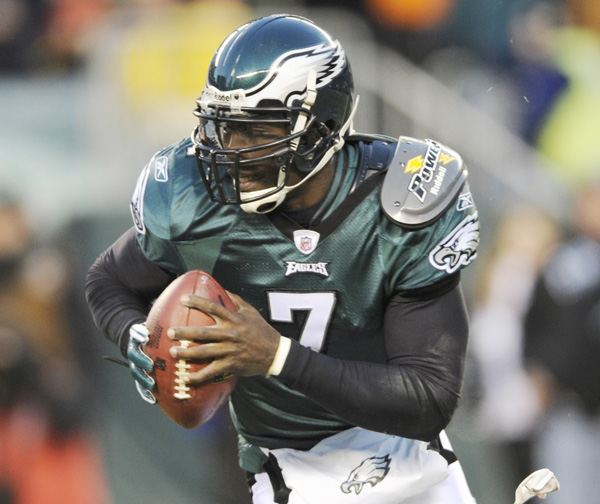 In this Jan. 9, 2011, photo, Philadelphia Eagles quarterback Michael Vick runs from a tackler during the first half of an NFL wild card playoff football game against the Green Bay Packers.