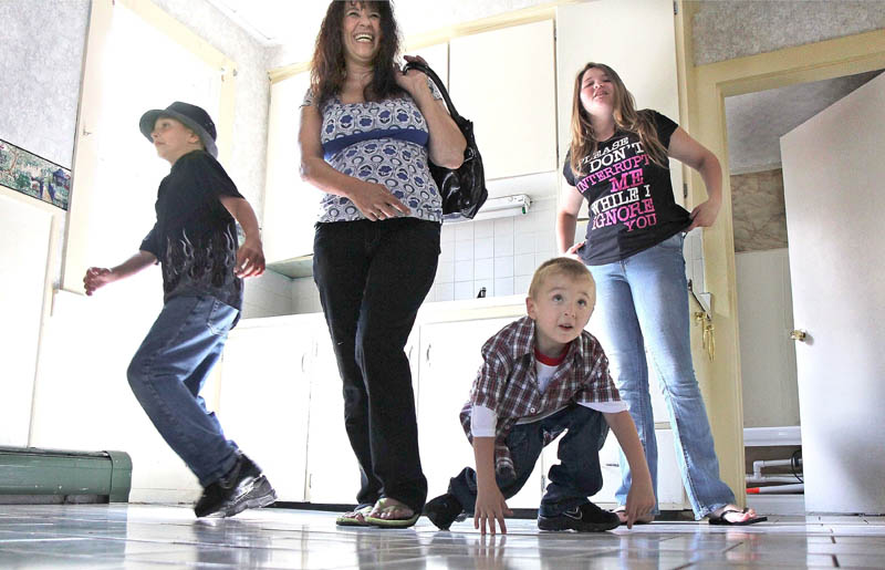 Tracey Bragdon and her three children Keatin, left, Keon, center, and Kaylynn, right, look over their new duplex apartment Thursday. The family lost their home on Oak Street in a fire on Tuesday.