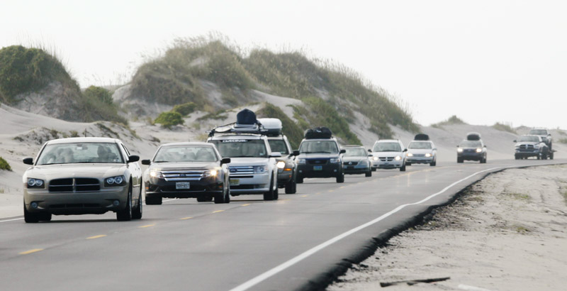With a mandatory visitor evacuation in place, cars drive north on Highway 12 on Pea Island, N.C., in North Carolina's Outer Banks today.