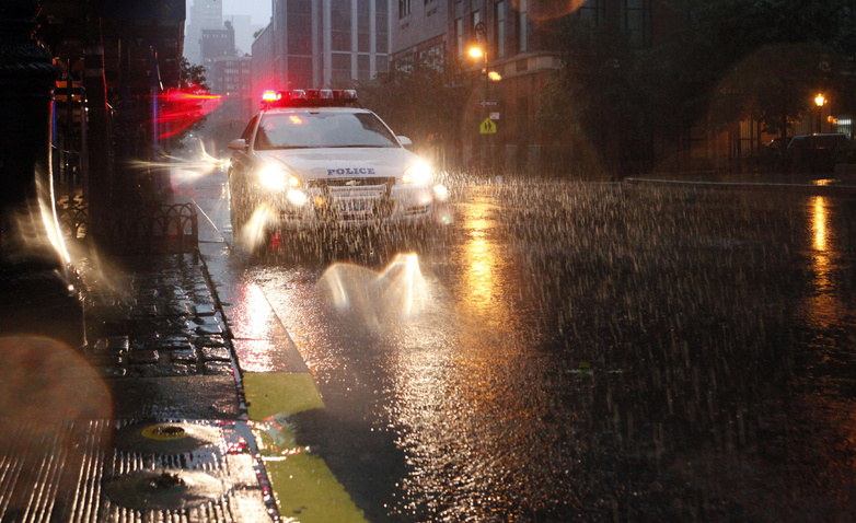 Heavy rain falls as a police car drives in Battery Park City in New York as Hurricane Irene approaches today. Battery Park City and other areas in Lower Manhattan were evacuated in advance of the storm.