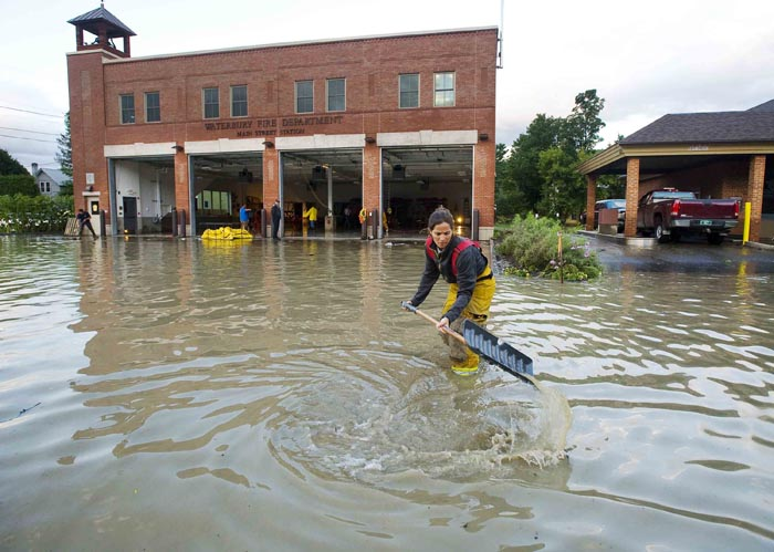 Firefighter Mandy Drake clears a storm drain today in front of the fire department in Waterbury, Vt., in the wake of tropical storm Irene. The building was evacuated as high water from the Winooski River flooded downtown Sunday. Almost 50,000 Vermont utility customers were without power today, hundreds of roads were closed and a number of bridges destroyed by the