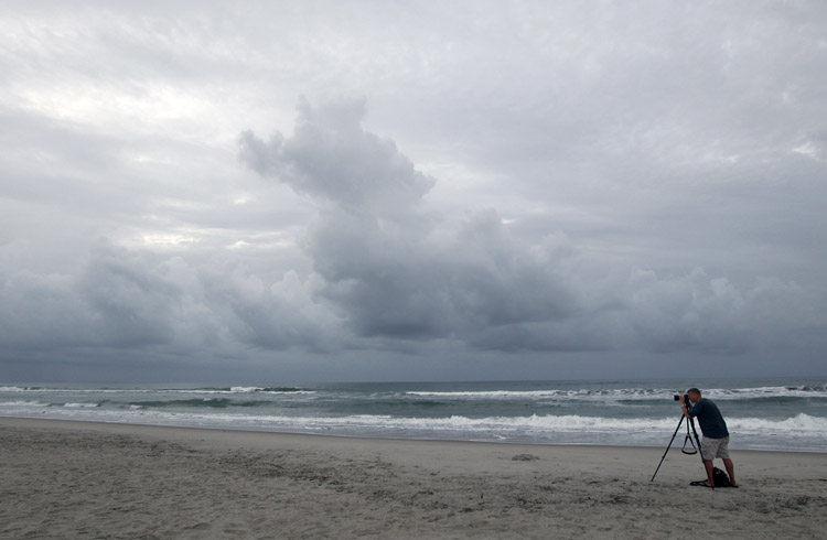 Cash Haggarty, of Washington, takes photos at daybreak in Atlantic Beach, N.C., today. A hurricane watch was issued early today for much of the North Carolina coast. Officials along the East Coast of the United States are calculating what they need to do if Irene becomes the first major hurricane to strike the region in seven years.
