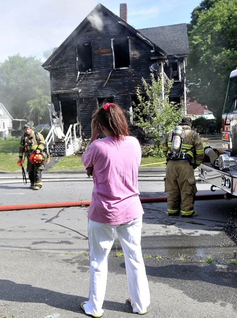 Staff photo by Michael G. Seamans Tracy Bragdon stands in front of her Oak Street home in Waterville, Tuesday morning, as Forty firefighters from four agencies including, Waterville, Winslow, Fairfield and Oakland Fire Departments, battle the blaze. No injuries were reported.