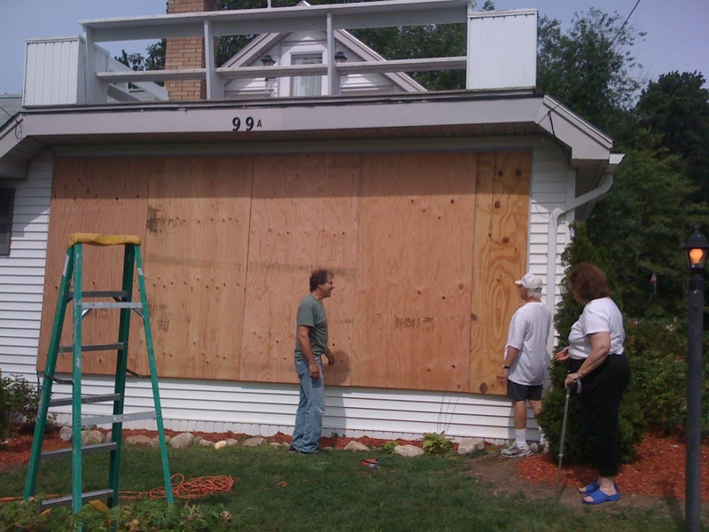 John and Clare Gambino, right, look at the work of Cape Elizabeth builder Larry Skillings as he puts up plywood panels to protect the large front picture window on their home on East Grand Ave. in Scarborough. It's the first time in the 32 years they've lived there that they have put up protection from any storm, according to the Gambinos.