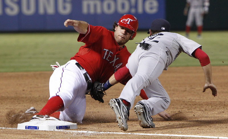 Texas Rangers' Ian Kinsler (5) beats the tag against Boston Red Sox third baseman Jed Lowrie (12) for the safe slide at third during the third inning of their game Monday in Arlington, Texas.