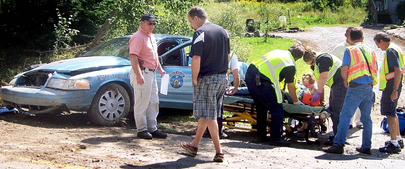 Emergency responders stabilize a state trooper after he crashed his cruiser on Industry Road in Farmington. Jeff Colameco, 50, of Sandwich, Mass., who was driving a pickup truck nearly hit by the cruiser, walks past the stretcher.