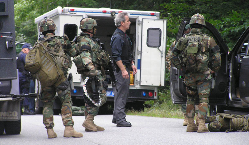 Staff photo by Scott Monroe State and local police converge on North Pond Road in Winslow Thursday afternoon where a man barricaded himself in a home and threatened to kill himself.