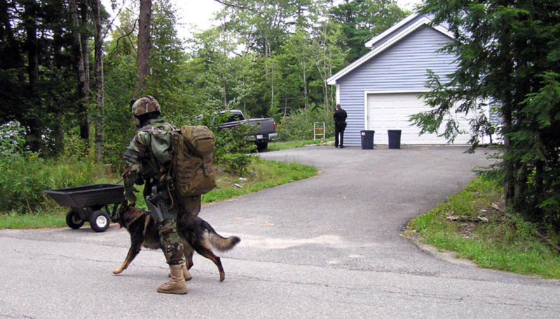 Staff photo by Scott Monroe A Maine State Police trooper runs by with a tracking dog on North Pond Road in Winslow Thursday afternoon where a man barricaded himself in a home and threatened to kill himself.