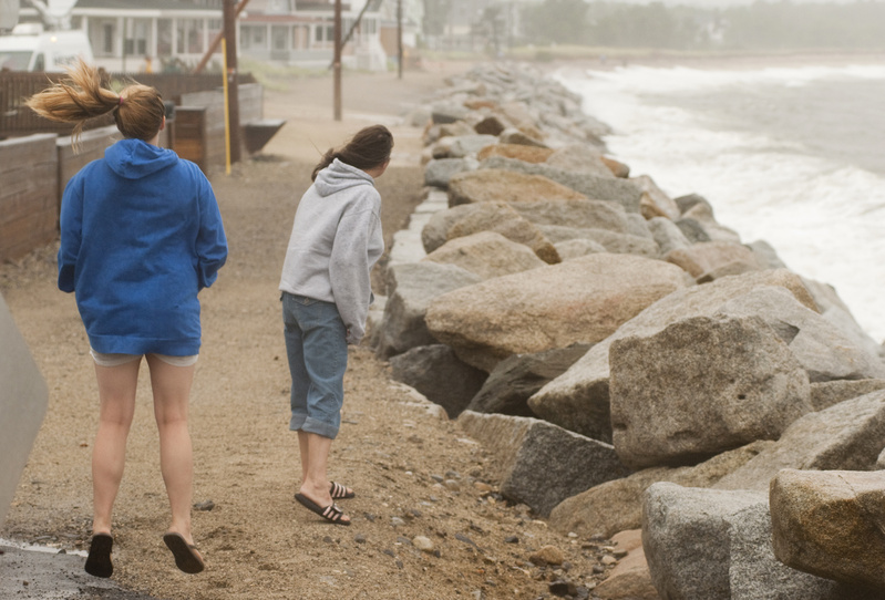 Alisha Bergeron, 17 of Saco jumps to get a better look while checking out the waves with her mother Kathy at high tide during Tropical Storm Irene along Surf Street in Camp Ellis, Saco, today.