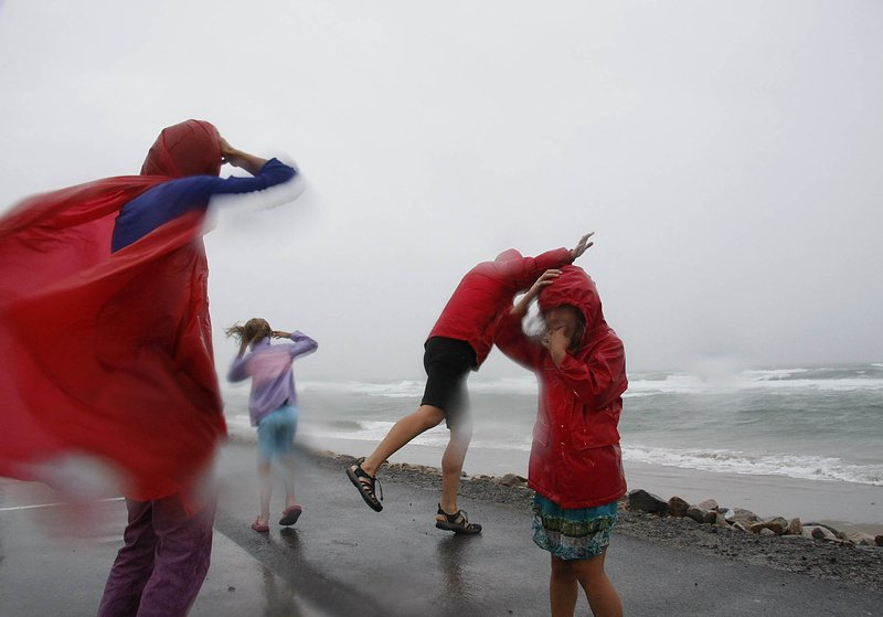 Kristen Day, far left, of Boston feels the powerful winds of Tropical Storm Irene with her family at Ogunquit Beach today while on vacation.