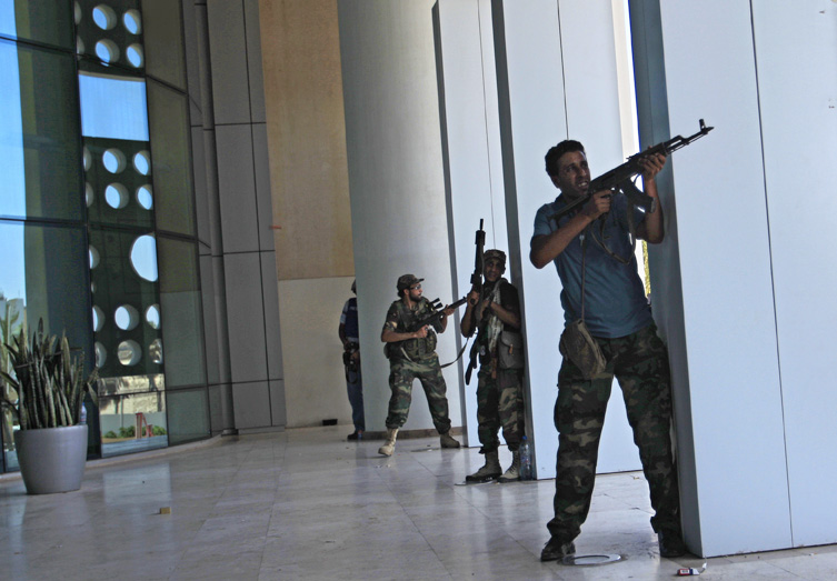 Rebel fighters take shelter as an intense gunbattle erupted outside the Corinthia hotel, where many foreign journalists are staying, in Tripoli today.
