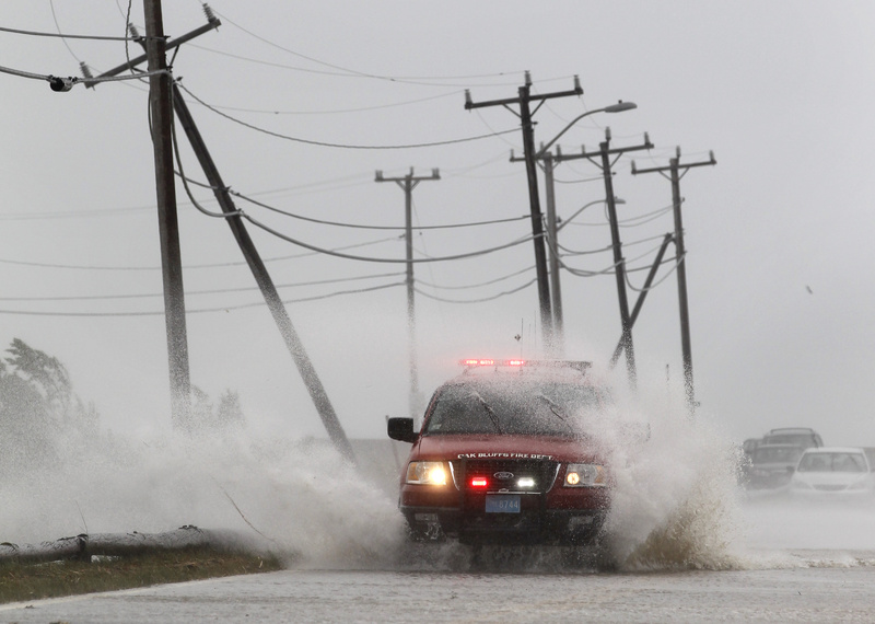 An Oak Bluffs fire department vehicle is buffeted by strong winds and ocean spray from Tropical Storm Irene while driving along a coastal road in Edgartown, Mass., on the island of Martha's Vineyard today.