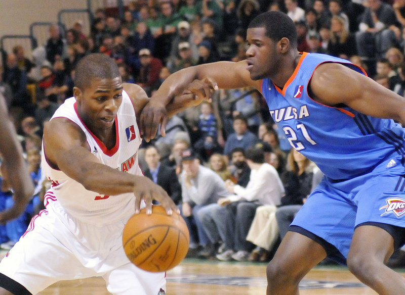 Maine Red Claw DeShawn Sims, left, fights off a Tulsa player in this January 2011 game. The franchise has sold out every game in its first two seasons at the Portland Expo, averaging 3,045 fans a game.